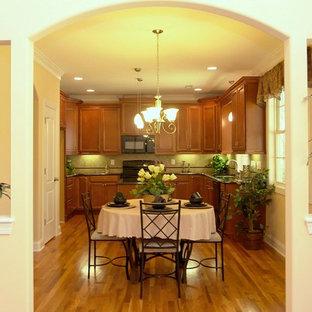 ローリーの中くらいのトラディショナルスタイルのおしゃれなキッチン (ダブルシンク、落し込みパネル扉のキャビネット、中間色木目調キャビネット、御影石カウンター、黒いキッチンパネル、セラミックタイルのキッチンパネル、黒い調理設備、淡色無垢フローリング) の写真