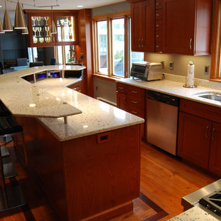 Mid-sized transitional l-shaped open plan kitchen in Boston with an undermount sink, shaker cabinets, medium wood cabinets, recycled glass benchtops, glass tile splashback, stainless steel appliances, medium hardwood floors, with island, beige splashback and brown floor.