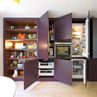Trendy light wood floor eat-in kitchen photo in London with flat-panel cabinets and white cabinets