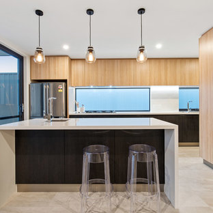 Inspiration for a contemporary kitchen in Perth with an undermount sink, flat-panel cabinets, light wood cabinets, white splashback, stainless steel appliances, with island, beige floor and white benchtop.
