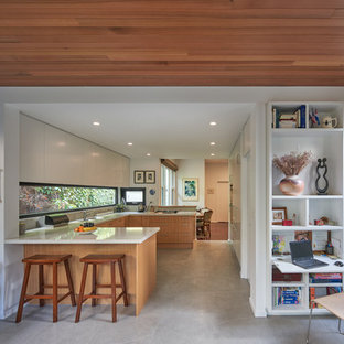 Photo of a mid-sized contemporary u-shaped kitchen in Melbourne with flat-panel cabinets, medium wood cabinets, window splashback, a peninsula, beige floor, a drop-in sink, panelled appliances and beige benchtop.
