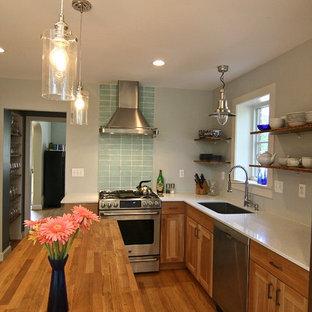 ワシントンD.C.の中サイズのコンテンポラリースタイルのおしゃれなキッチン (アンダーカウンターシンク、落し込みパネル扉のキャビネット、中間色木目調キャビネット、再生ガラスカウンター、緑のキッチンパネル、ガラスタイルのキッチンパネル、シルバーの調理設備、無垢フローリング) の写真