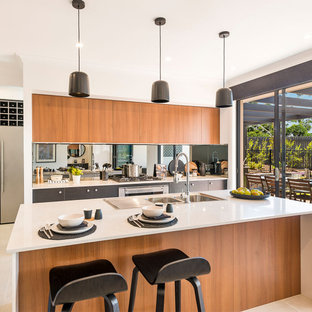 This is an example of a large contemporary galley open plan kitchen in Canberra - Queanbeyan with shaker cabinets, dark wood cabinets, quartz benchtops, metallic splashback, mirror splashback, stainless steel appliances, ceramic floors, with island, beige floor and yellow benchtop.