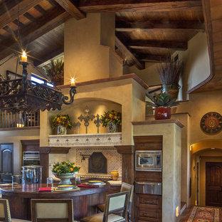 フェニックスのサンタフェスタイルのおしゃれなキッチン (シェーカースタイル扉のキャビネット、中間色木目調キャビネット、ベージュキッチンパネル、トラバーチンのキッチンパネル、シルバーの調理設備、無垢フローリング、茶色い床) の写真