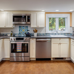 Traditional kitchen appliance - Elegant u-shaped cork floor and brown floor kitchen photo in Boston with a drop-in sink, shaker cabinets, soapstone countertops, multicolored backsplash, ceramic backsplash, stainless steel appliances, no island, black countertops and beige cabinets