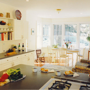 Photo of a large traditional l-shaped kitchen in Boston with a double-bowl sink, flat-panel cabinets, white cabinets, laminate benchtops, grey splashback, white appliances, ceramic floors and a peninsula.