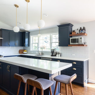 Inspiration for a transitional l-shaped eat-in kitchen in Chicago with an undermount sink, shaker cabinets, blue cabinets, quartz benchtops, blue splashback, glass tile splashback, stainless steel appliances, dark hardwood floors, with island, brown floor and white benchtop.