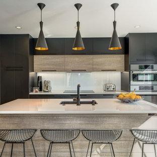 ワシントンD.C.の中サイズのコンテンポラリースタイルのおしゃれなキッチン (フラットパネル扉のキャビネット、黒いキャビネット、珪岩カウンター、白いキッチンパネル、ガラス板のキッチンパネル、磁器タイルの床、ベージュの床、白いキッチンカウンター、アンダーカウンターシンク、パネルと同色の調理設備) の写真