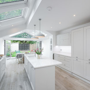 Traditional galley kitchen/diner in Other with stainless steel appliances, an island, a submerged sink, shaker cabinets, white cabinets, white splashback, light hardwood flooring and beige floors.