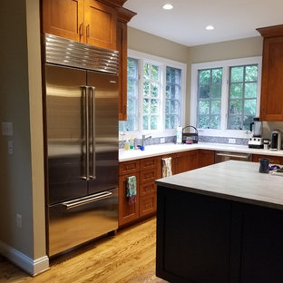 This is an example of a mid-sized transitional l-shaped eat-in kitchen in DC Metro with an integrated sink, recessed-panel cabinets, medium wood cabinets, solid surface benchtops, blue splashback, mosaic tile splashback, stainless steel appliances, medium hardwood floors, a peninsula, brown floor and blue benchtop.