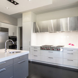 Mid-sized modern eat-in kitchen pictures - Inspiration for a mid-sized modern u-shaped dark wood floor and black floor eat-in kitchen remodel in DC Metro with an undermount sink, flat-panel cabinets, white cabinets, solid surface countertops, stainless steel appliances, an island, metallic backsplash and mirror backsplash