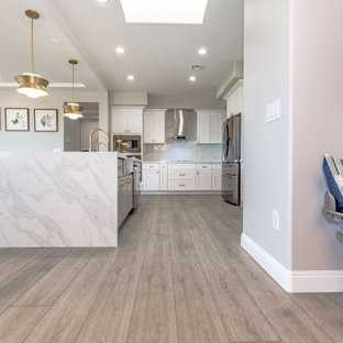 Expansive asian u-shaped eat-in kitchen in Las Vegas with a farmhouse sink, white cabinets, white splashback, marble splashback, stainless steel appliances, vinyl floors, with island, grey floor, white benchtop, recessed-panel cabinets and quartz benchtops.