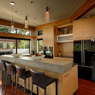 Inspiration for a contemporary l-shaped open plan kitchen in Vancouver with flat-panel cabinets, light wood cabinets, concrete benchtops, window splashback, black appliances, dark hardwood floors, with island and red floor.