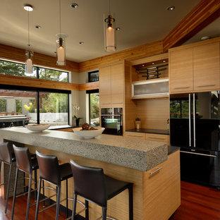 バンクーバーのコンテンポラリースタイルのおしゃれなキッチン (フラットパネル扉のキャビネット、淡色木目調キャビネット、コンクリートカウンター、ガラスまたは窓のキッチンパネル、黒い調理設備、濃色無垢フローリング、赤い床) の写真