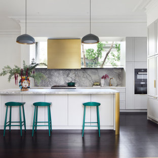 This is an example of a mid-sized transitional open plan kitchen in Melbourne with a double-bowl sink, white cabinets, marble benchtops, multi-coloured splashback, marble splashback, black appliances, dark hardwood floors, with island, brown floor, white benchtop and shaker cabinets.
