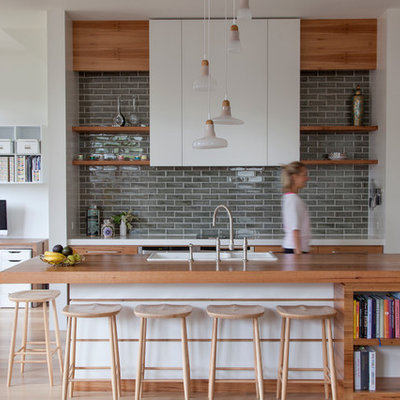 Example of a large trendy galley light wood floor kitchen design in Melbourne with a drop-in sink, flat-panel cabinets, medium tone wood cabinets, wood countertops, gray backsplash, stainless steel appliances, an island and subway tile backsplash