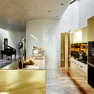 Photo of a contemporary galley open plan kitchen in Melbourne with an undermount sink, flat-panel cabinets, yellow cabinets, metallic splashback, metal splashback, black appliances, with island and grey floor.