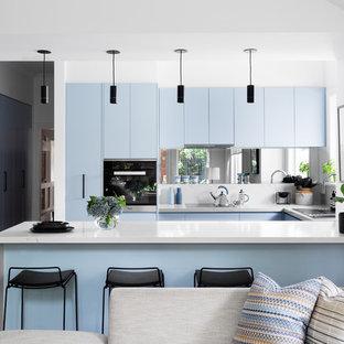 Свежая идея для дизайна: п-образная кухня-гостиная в современном стиле с накладной раковиной, плоскими фасадами, синими фасадами, фартуком цвета металлик, фартуком из зеркальной плитки, техникой из нержавеющей стали, светлым паркетным полом, полуостровом и коричневым полом - отличное фото интерьера