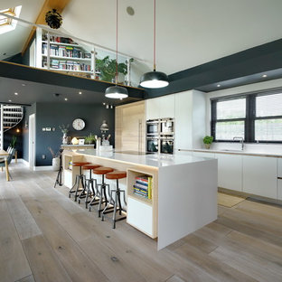 This is an example of a large contemporary single-wall open plan kitchen in Other with a submerged sink, flat-panel cabinets, white cabinets, light hardwood flooring, an island, beige floors and white splashback.