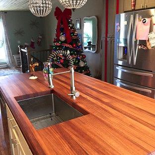 Неиссякаемый источник вдохновения для домашнего уюта: параллельная кухня среднего размера в современном стиле с обеденным столом, врезной раковиной, фасадами с выступающей филенкой, белыми фасадами, столешницей из дерева, техникой из нержавеющей стали, полом из керамической плитки, островом, коричневым полом и красной столешницей