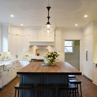 This is an example of a large contemporary u-shaped eat-in kitchen in Denver with a farmhouse sink, white cabinets, wood benchtops, white splashback, ceramic splashback, white appliances, dark hardwood floors, with island, brown floor and red benchtop.