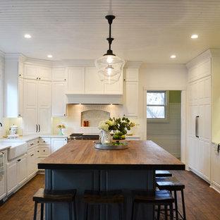 На фото: большая п-образная кухня в современном стиле с обеденным столом, раковиной в стиле кантри, белыми фасадами, столешницей из дерева, белым фартуком, фартуком из керамической плитки, белой техникой, темным паркетным полом, островом, коричневым полом и красной столешницей с