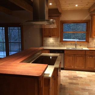 ニューアークの中サイズのコンテンポラリースタイルのおしゃれなキッチン (アンダーカウンターシンク、レイズドパネル扉のキャビネット、中間色木目調キャビネット、木材カウンター、ベージュキッチンパネル、セラミックタイルのキッチンパネル、シルバーの調理設備の、セラミックタイルの床、茶色い床、赤いキッチンカウンター) の写真
