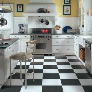 他の地域の中サイズのカントリー風おしゃれなキッチン (エプロンフロントシンク、フラットパネル扉のキャビネット、白いキャビネット、人工大理石カウンター、白いキッチンパネル、木材のキッチンパネル、シルバーの調理設備の、磁器タイルの床、黒い床) の写真