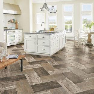 他の地域の中サイズのカントリー風おしゃれなキッチン (シェーカースタイル扉のキャビネット、白いキャビネット、アンダーカウンターシンク、人工大理石カウンター、白いキッチンパネル、サブウェイタイルのキッチンパネル、シルバーの調理設備の、磁器タイルの床、茶色い床) の写真