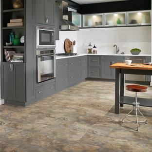 オーランドのインダストリアルスタイルのおしゃれなキッチン (アンダーカウンターシンク、シェーカースタイル扉のキャビネット、グレーのキャビネット、珪岩カウンター、白いキッチンパネル、サブウェイタイルのキッチンパネル、シルバーの調理設備の、スレートの床、ベージュの床) の写真
