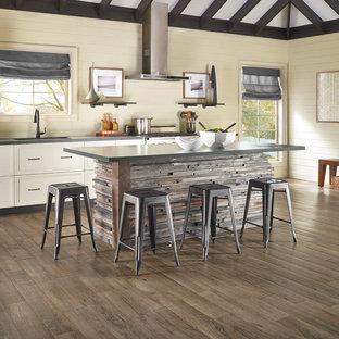 Cette image montre une grand cuisine ouverte linéaire chalet avec un évier encastré, un placard à porte shaker, des portes de placard blanches, un plan de travail en zinc, une crédence beige, une crédence en bois, un sol en bois brun et un îlot central.