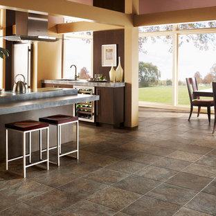 ロサンゼルスの中サイズのコンテンポラリースタイルのおしゃれなキッチン (アンダーカウンターシンク、フラットパネル扉のキャビネット、濃色木目調キャビネット、木材のキッチンパネル、シルバーの調理設備の、クッションフロア、コンクリートカウンター、茶色いキッチンパネル、マルチカラーの床) の写真