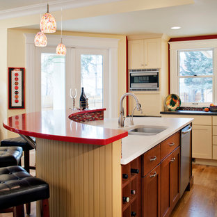 Photo of a traditional kitchen in Denver with a double-bowl sink, recessed-panel cabinets, medium wood cabinets and red benchtop.