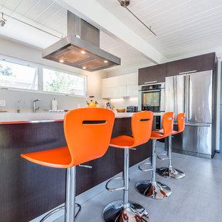 サンフランシスコの大きいモダンスタイルのおしゃれなキッチン (アンダーカウンターシンク、フラットパネル扉のキャビネット、茶色いキャビネット、クオーツストーンカウンター、シルバーの調理設備、コンクリートの床、グレーの床) の写真