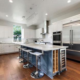 Idéer för stora vintage vitt kök, med en rustik diskho, skåp i shakerstil, vita skåp, bänkskiva i kvartsit, vitt stänkskydd, rostfria vitvaror, mellanmörkt trägolv, en köksö, brunt golv och glaspanel som stänkskydd