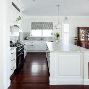 ブリスベンの中くらいのトラディショナルスタイルのおしゃれなキッチン (アンダーカウンターシンク、シェーカースタイル扉のキャビネット、白いキャビネット、大理石カウンター、ベージュキッチンパネル、セメントタイルのキッチンパネル、黒い調理設備、濃色無垢フローリング、赤い床、ベージュのキッチンカウンター) の写真