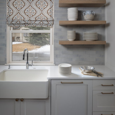 Example of a small transitional l-shaped brown floor and medium tone wood floor open concept kitchen design in Denver with a farmhouse sink, shaker cabinets, gray cabinets, quartz countertops, gray backsplash, subway tile backsplash, stainless steel appliances, an island and white countertops