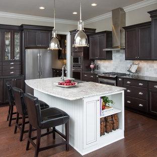 Klassisk inredning av ett stort l-kök, med luckor med infälld panel, skåp i mörkt trä, flerfärgad stänkskydd, rostfria vitvaror, mellanmörkt trägolv, en köksö, orange golv och stänkskydd i tunnelbanekakel