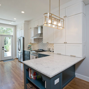 Inspiration for a small modern u-shaped eat-in kitchen in DC Metro with a farmhouse sink, recessed-panel cabinets, white cabinets, quartz benchtops, white splashback, ceramic splashback, stainless steel appliances, medium hardwood floors, a peninsula and blue benchtop.
