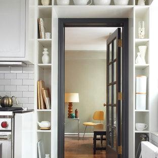 Idée de décoration pour une petite cuisine urbaine en U avec un placard avec porte à panneau encastré, une crédence en carrelage métro, un électroménager en acier inoxydable, une crédence blanche, des portes de placard blanches et un sol en bois foncé.