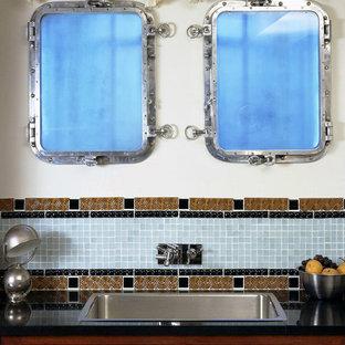 ニューヨークの巨大なエクレクティックスタイルのおしゃれなキッチン (ドロップインシンク、レイズドパネル扉のキャビネット、中間色木目調キャビネット、御影石カウンター、青いキッチンパネル、ガラスタイルのキッチンパネル、パネルと同色の調理設備、セラミックタイルの床、黄色い床) の写真