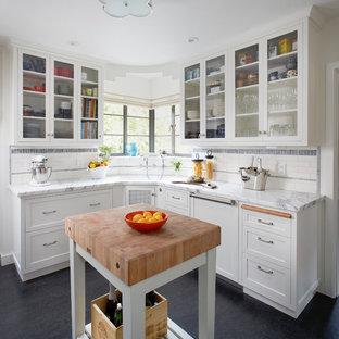 Klassisk inredning av ett mellanstort vit vitt l-kök, med vita skåp, marmorbänkskiva, stänkskydd i keramik, linoleumgolv, en köksö, luckor med glaspanel, flerfärgad stänkskydd och svart golv
