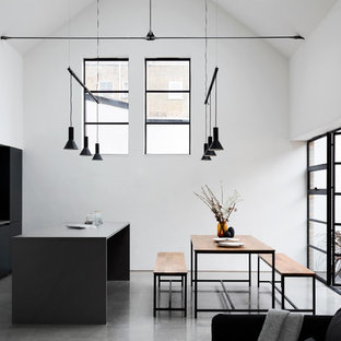 Photo of a modern open plan kitchen in Other with flat-panel cabinets, black cabinets, black splashback, black appliances, concrete flooring, an island, grey floors and grey worktops.