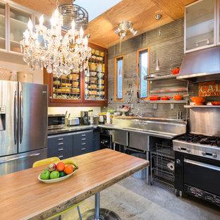 Immagine di una cucina a L boho chic chiusa con lavello a doppia vasca, ante di vetro, pavimento in cemento e elettrodomestici in acciaio inossidabile