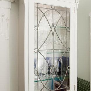 Diseño de cocina en U, de estilo americano, pequeña, con despensa, fregadero bajoencimera, armarios con paneles lisos, puertas de armario blancas, encimera de granito, salpicadero gris, salpicadero de azulejos de vidrio, electrodomésticos con paneles y suelo de pizarra