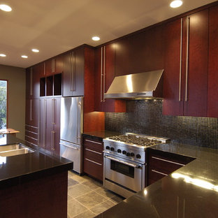 Example of an eclectic l-shaped eat-in kitchen design in San Francisco with stainless steel appliances, a double-bowl sink, flat-panel cabinets, dark wood cabinets, black backsplash, mosaic tile backsplash and granite countertops