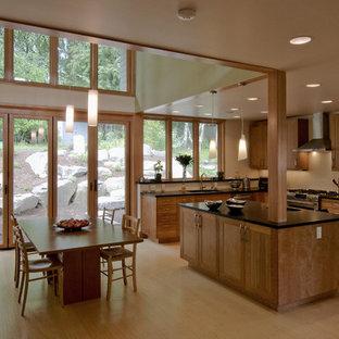 シアトルのアジアンスタイルのおしゃれなダイニングキッチン (アンダーカウンターシンク、シェーカースタイル扉のキャビネット、中間色木目調キャビネット、御影石カウンター、シルバーの調理設備の) の写真