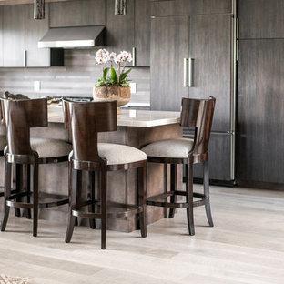 オレンジカウンティの中サイズのモダンスタイルのおしゃれなキッチン (シェーカースタイル扉のキャビネット、濃色木目調キャビネット、人工大理石カウンター、茶色いキッチンパネル、木材のキッチンパネル、パネルと同色の調理設備、淡色無垢フローリング、ベージュの床、ベージュのキッチンカウンター) の写真