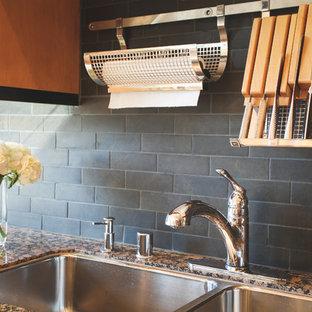 フェニックスの中くらいのインダストリアルスタイルのおしゃれなキッチン (ダブルシンク、フラットパネル扉のキャビネット、御影石カウンター、磁器タイルのキッチンパネル、シルバーの調理設備、無垢フローリング、中間色木目調キャビネット、グレーのキッチンパネル) の写真
