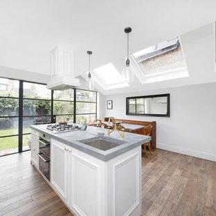 ロンドンの中サイズのエクレクティックスタイルのおしゃれなキッチン (アンダーカウンターシンク、インセット扉のキャビネット、白いキャビネット、亜鉛製カウンター、無垢フローリング、茶色い床、グレーのキッチンカウンター) の写真